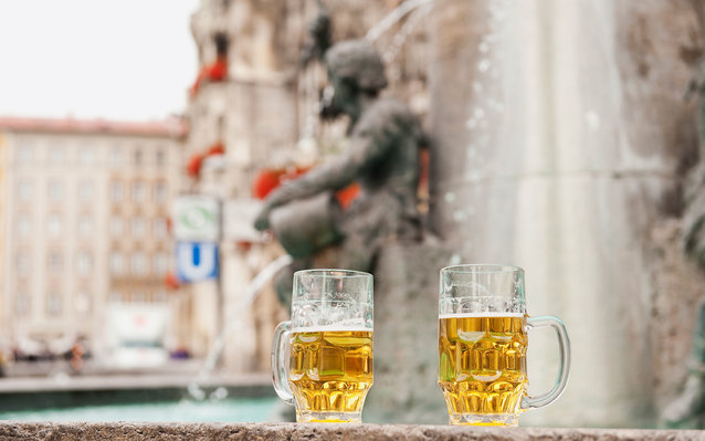 Germany, Bavaria, Munich, Marienplatz, Two beer mugs with fountain in background, close-up